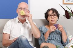 Happy senior couple drinking coffee, in their sofa. An happy senior couple drinking coffee, in their sofa Stock Photography