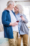 Happy senior couple drinking wine in art workshop. Side view of happy senior couple drinking wine in art workshop Royalty Free Stock Photos