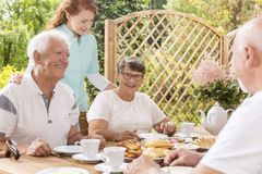 Happy senior couple eating breakfast and a nurse taking care of. Them in the garden royalty free stock photo