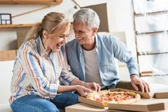 happy senior couple eating pizza and laughing stock image