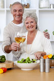 Happy senior couple eating a salad in the kitchen Royalty Free Stock Photos