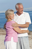 Happy Senior Couple Embracing on Beach Stock Photography