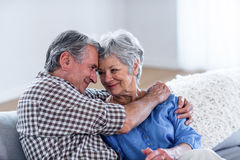 Happy senior couple embracing each other on sofa Royalty Free Stock Photos