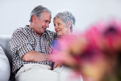 Happy senior couple embracing each other on sofa Stock Photo