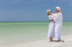 Happy Senior Couple Embracing on A Tropical Beach. Happy senior man and woman embracing on a deserted tropical beach with bright clear blue sky Stock Photography