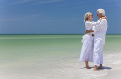 Happy Senior Couple Embracing on Tropical Beach. Happy senior men and women couple together embracing by sea on a deserted tropical beach with bright clear blue Stock Photography