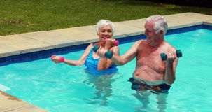 Senior couple exercising with dumbbells in the pool. Happy senior couple exercising with dumbbells in the pool stock video