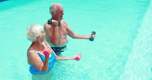 Senior couple exercising with dumbbells in the pool. Happy senior couple exercising with dumbbells in the pool stock footage