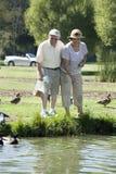 Happy Senior Couple Feeding Ducks Royalty Free Stock Photo
