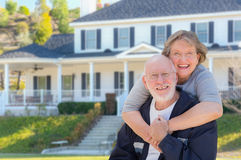 Happy Senior Couple in Front of House. Attractive Happy Senior Couple in Front Yard of House stock photos