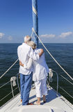 Happy Senior Couple On Front of a Sail Boat Stock Photo