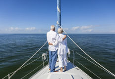 Happy Senior Couple On Front of a Sail Boat. A happy senior couple embracing at the front or bow of a sail boat on a calm blue sea looking to an clear horizon Royalty Free Stock Image
