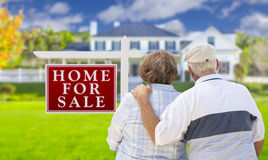 Happy Senior Couple Front of For Sale Sign and House Stock Image