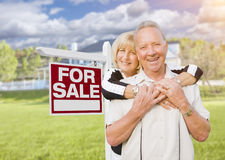 Happy Senior Couple Front of For Sale Sign and House Royalty Free Stock Images