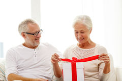 Happy senior couple with gift box at home Royalty Free Stock Photo
