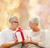 Happy senior couple with gift box at home Royalty Free Stock Images