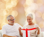 Happy senior couple with gift box at home. Family, holidays, christmas, age and people concept - happy senior couple with gift box over beige lights background Royalty Free Stock Photos