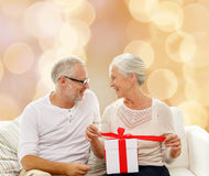 Happy senior couple with gift box at home. Family, holidays, christmas, age and people concept - happy senior couple with gift box over beige lights background Royalty Free Stock Image