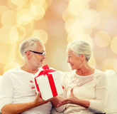 Happy senior couple with gift box at home. Family, holidays, christmas, age and people concept - happy senior couple with gift box over beige lights background Royalty Free Stock Images
