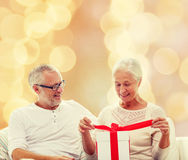 Happy senior couple with gift box at home. Family, holidays, christmas, age and people concept - happy senior couple with gift box over beige lights background Stock Photos