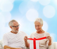 Happy senior couple with gift box at home Stock Image