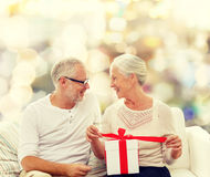 Happy senior couple with gift box at home Stock Photography