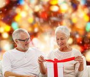 Happy senior couple with gift box at home Stock Photos
