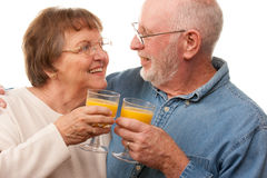 Happy Senior Couple with Glasses of Orange Juice Royalty Free Stock Photos