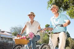 Happy senior couple going for a bike ride in the city Royalty Free Stock Photography