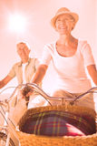 Happy senior couple going for a bike ride Stock Image