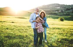 Senior couple with granddaughter standing outside in spring nature at sunset. Happy senior couple with granddaughter standing outside in spring nature at sunset stock photography