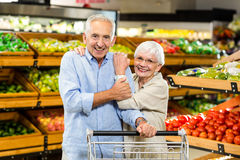 Happy senior couple at the grocery shop. Looking at the camera Stock Photography