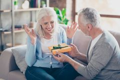 Happy senior couple having anniversary day, bearded husband pres. Enting a packing gift for his wife, women looks exciting, happy, surprised, she raised her stock image
