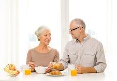 Happy senior couple having breakfast at home Stock Photos