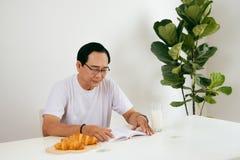Happy senior couple having croissant and milk breakfast at home,. Reading book Stock Photos