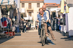 Happy senior couple having fun with bicycle at flea market. Concept of active playful elderly with bike during retirement - Everyday joy lifestyle without age royalty free stock photo