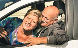 Happy senior couple having fun driving car trip on the road. Joyful active elderly concept with retired men and women enjoying best years - Modern mature Royalty Free Stock Images