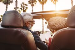 Happy senior couple having fun on new convertible car - Mature people enjoying time together during road trip vacation
