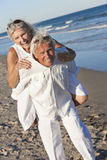 Happy Senior Couple Having Fun on A Tropical Beach. Happy senior men and women couple playing piggy back and having fun on a deserted tropical beach Stock Photo