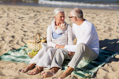 Happy senior couple having picnic on summer beach Stock Image