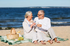 Happy senior couple having picnic on summer beach Stock Photo