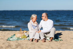 Happy senior couple having picnic on summer beach Stock Photography