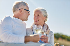 Happy senior couple having picnic on summer beach. Family, age, holidays, leisure and people concept - happy senior couple having picnic and clinking wine Royalty Free Stock Photo