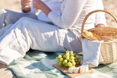 Happy senior couple having picnic on summer beach. Family, age, holidays, leisure and people concept - close up of happy senior couple with picnic basket sitting Stock Photos
