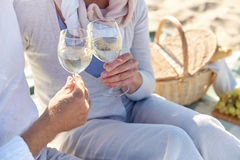 Happy senior couple having picnic on summer beach. Family, age, holidays, leisure and people concept - close up of happy senior couple having and clinking wine royalty free stock images