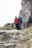 Happy senior couple hiking on rocky terrain Stock Photography