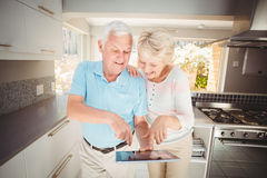 Happy senior couple holding digital tablet in kitchen Royalty Free Stock Images