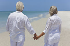 Happy Senior Couple Holding Hands on A Beach. Rear view of a happy senior man and woman couple together holding hands and looking out to sea on a deserted Stock Photo