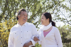 Happy senior couple holding hands and going for a walk in the park in springtime, Beijing Stock Photography