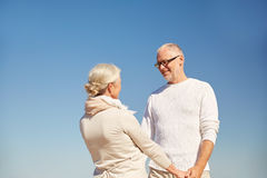 Happy senior couple holding hands outdoors Stock Images